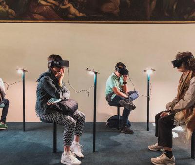 personnes assises utilisant la réalité virtuel au musée